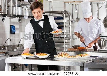Young waiter placing dishes in tray with chef working in commercial kitchen - stock photo