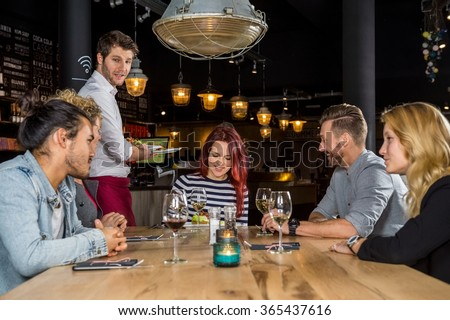Young waiter serving food to male and female customers at table in cafe - stock photo