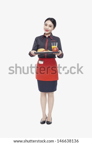 Young Waitress carrying tray with food, studio shot - stock photo