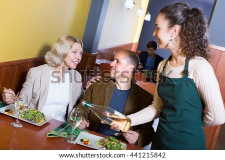 Young waitress serving positive mature couple at dinner in cafe