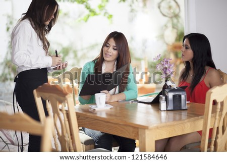 Young waitress taking an order from her customers at a coffee shop