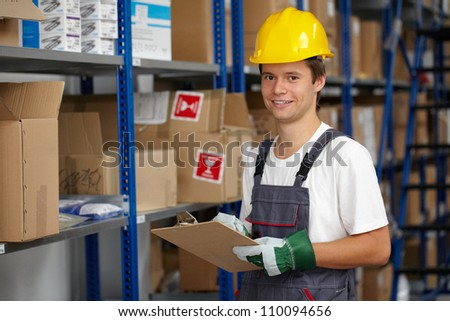 Young warehouse worker do some stock check - stock photo