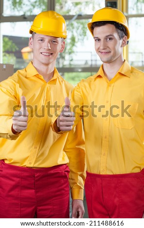 Young warehouse workers showing thumbs up sign - stock photo