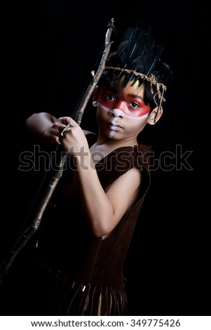 Young Warrior.  Young mixed race boy dressed as a Native American and holding a bow and arrow.  Dramatic lighting for effect. - stock photo