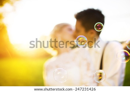 Young wedding couple enjoying romantic moments outside in a summer park. - stock photo