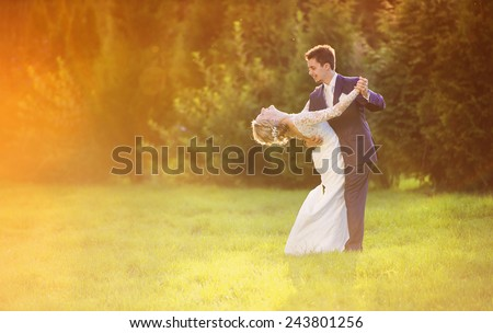 Young wedding couple enjoying romantic moments outside in summer park - stock photo