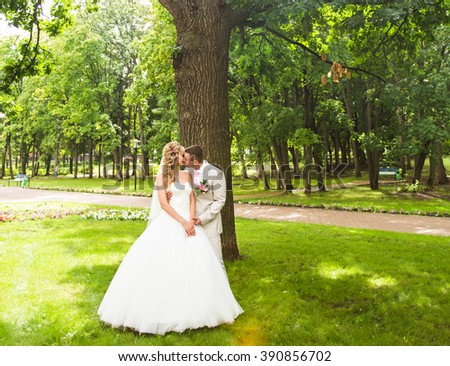 Young wedding couple enjoying romantic moments outside on a summer park