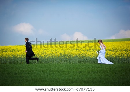 young wedding couple - freshly wed groom and bride posing outdoors on their wedding day, running through fields