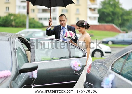 Young wedding couple getting in a car