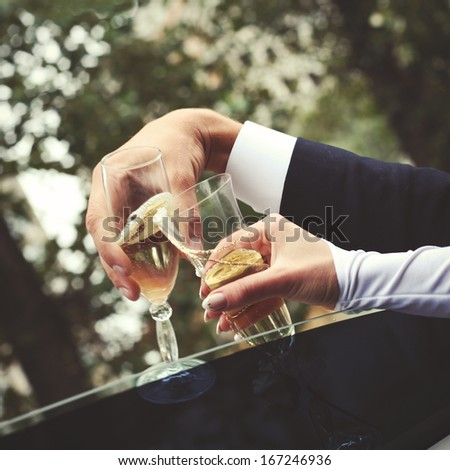 Young wedding couple holding glasses of champagne, sitting in car. - stock photo