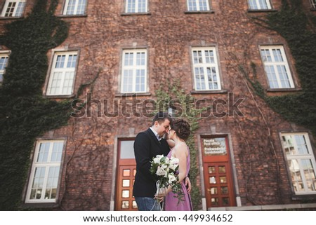 Young wedding couple in love story, bride and groom posing near building on the background. Krakow - stock photo