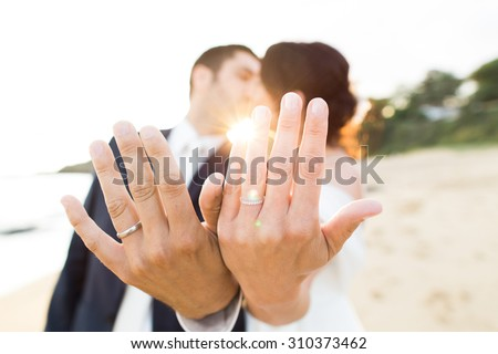 Young wedding couple on a beach showing their rings. Focus on hands