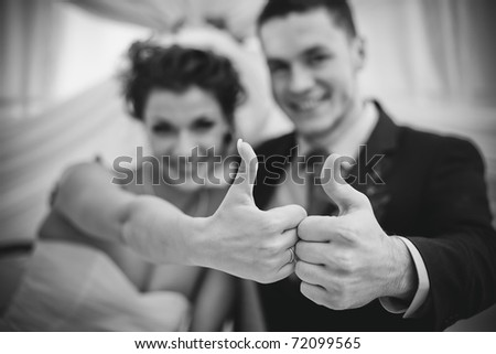Young wedding couple showing success sign. Focus on hands. - stock photo