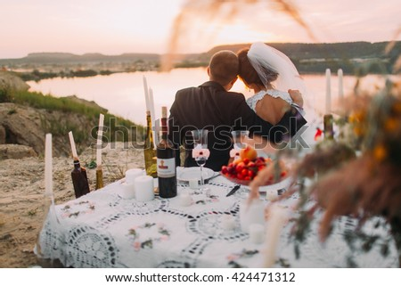 Young wedding couple siiting back to lake at romantic evening with candles on the sand beach - stock photo