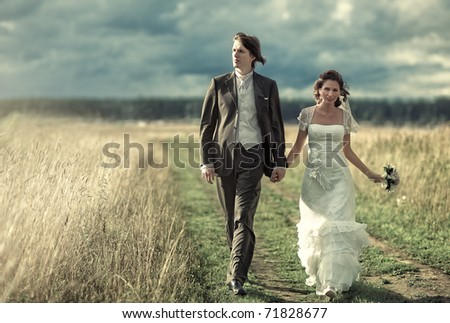 Young wedding couple walking on field. - stock photo