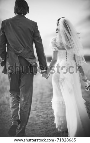 Young wedding couple walking on field. Retro style black and white colors.