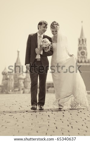Young wedding couple walking on Red Square. Retro colors. - stock photo