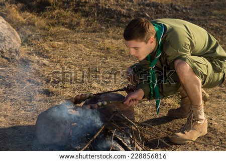 Young White Boy Scout Making Fire Out From Wood for Cooking at Campground. - stock photo