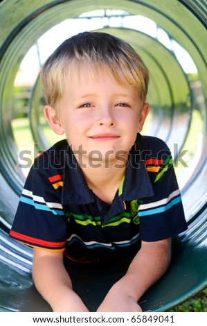 Young white boy sits in tunnel at the playground - stock photo