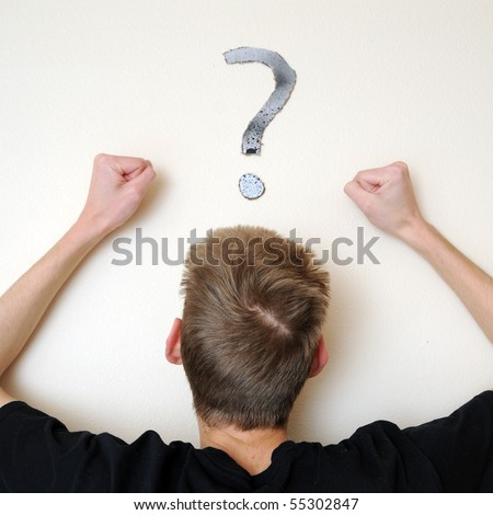 Young white Caucasian male adult staring forward, confused, with a question mark above his head on the wall. Focus point is on the person's head.