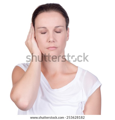 Young white deaf or hearing impaired woman with closed eyes holding her hand over her ear to shut out noise on white background in studio - stock photo