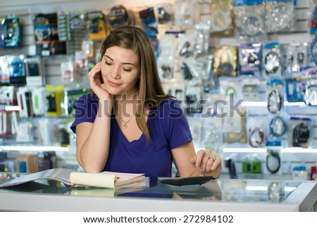 Young white female entrepreneur running a small business and working in a computer shop, and checking bills and invoice with calculator, doing budget and reviewing expenses. - stock photo
