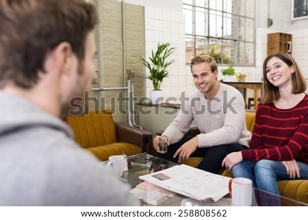 Young White Friends Relaxing at the Lounge Room While Sharing Happy Moments During their Break Time. - stock photo
