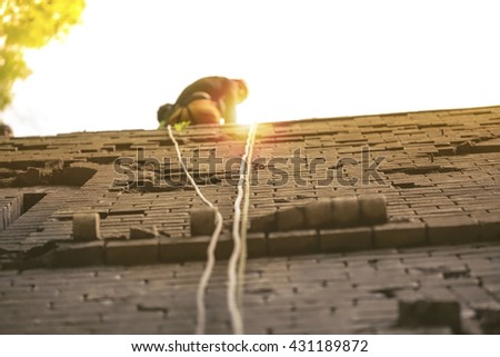 Young white man climbing a steep wall - stock photo