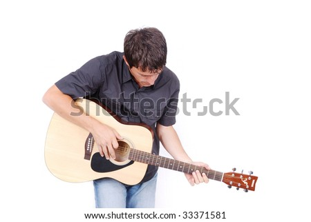 Young white man is holding a guitar and playing - stock photo