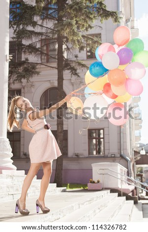 Young white woman holding colorful latex balloons, urban scene, outdoors - stock photo
