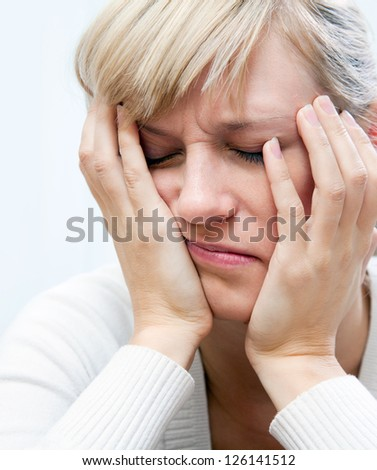 young white woman sadly sitting with his head propped on his hands - stock photo