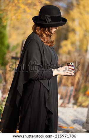 Young widow is standing at husband's tomb and meditating - stock photo
