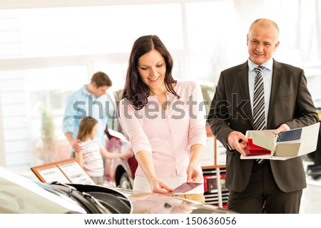 Young wife choosing the color of family car - stock photo