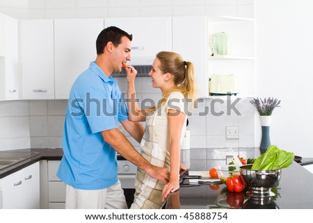 young wife let husband tasting the food in kitchen - stock photo