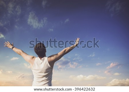 Young winner looking at blue sky with clouds