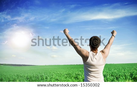Young winner man looking at blue sky with clouds - stock photo