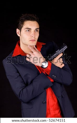 Young wise guy in a suit and red shirt holding a gun - stock photo