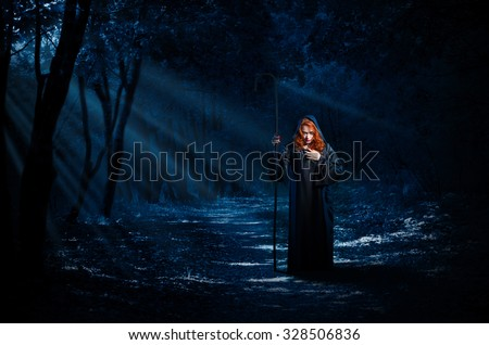 Young witch in night forest - stock photo