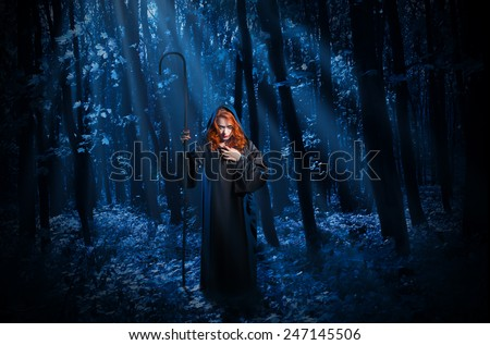 Young witch with staff in night forest - stock photo