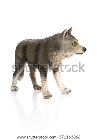 Young wolf toy. Isolated young spotty wolf toy standing on white background profile view. - stock photo