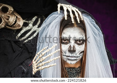 Young woman a bride in a veil day of the dead mask skull face art and