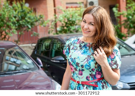 Young woman a driver standing next to vehicle, summer dress, copyspace - stock photo