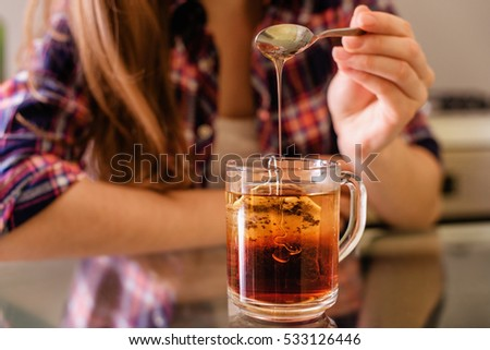 young woman add honey into tea