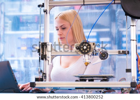 Young woman adjusting 3d printer - stock photo