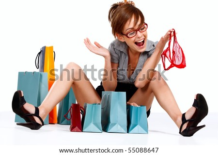 Young woman admiring her shopping getting red lingerie out of the shopping bag - stock photo
