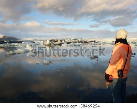 Young woman admiring Jokulsarlon, a lake in Iceland, where icebergs collapsing from Vatnajokull glacier are floating around.