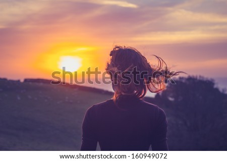 Young woman admiring the sunset over fields - stock photo