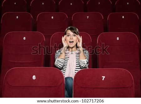 Young woman afraid of the movie at the cinema - stock photo