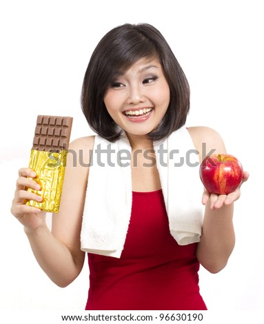 young woman after exercise holding chocolate and apple making a choice - stock photo