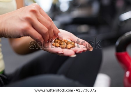Young woman after exercising eating almonds - stock photo